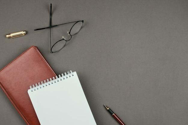 Modello minimalista alla moda con il taccuino, il pianificatore, i vetri e la penna su fondo grigio su copyspace Foto Premium