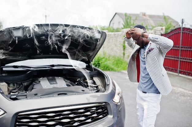 Un elegante e ricco uomo afroamericano in piedi davanti a un'auto suv rotta ha bisogno di assistenza guardando sotto il cofano aperto con il fumo. Foto Premium
