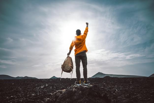 Escursionista di successo che fa un'escursione in montagna che punta al tramonto. Foto Premium