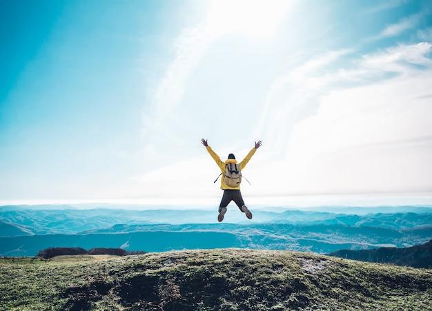 Uomo di successo che salta sulla cima della montagna Foto Premium