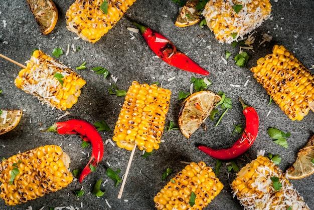 Cibo estivo. idee per grigliate e grigliate. mais alla griglia grigliato sul fuoco. con una spolverata di formaggio (elotes messicani), peperoncino e limone. su un tavolo di pietra scura. copia spazio Foto Premium