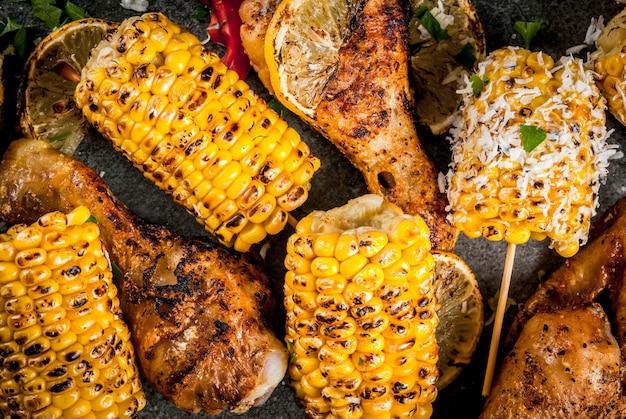 Cibo estivo. idee per barbecue, grigliate. mais e pollo (zampe, ali) grigliati, fritti a fuoco. con una spolverata di formaggio (elote), peperoncino piccante, limone. tavolo in pietra scura. chiudi vista dall'alto Foto Premium