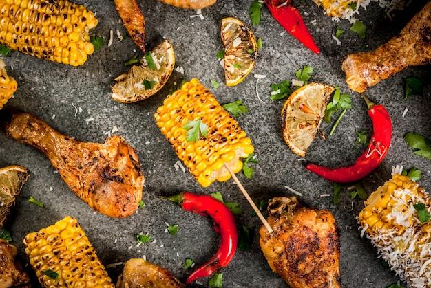 Cibo estivo. idee per barbecue, grigliate. mais e pollo (zampe, ali) grigliati, fritti a fuoco. con una spolverata di formaggio (elote), peperoncino piccante, limone. tavolo in pietra scura. copia spazio vista dall'alto Foto Premium
