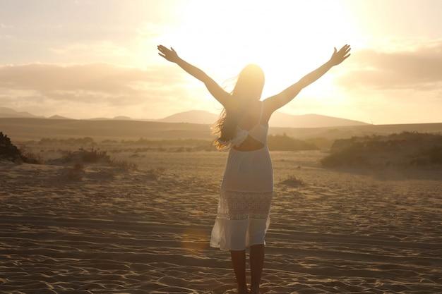 Tramonto nel deserto. giovane donna con le braccia alzate che indossa un abito bianco che cammina nella sabbia delle dune del deserto durante il tramonto. ragazza sulla sabbia dorata su corralejo dunas, fuerteventura. Foto Premium