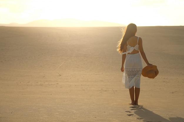 Tramonto nel deserto. giovane donna con vestito bianco che cammina tra le dune del deserto con orme nella sabbia durante il tramonto. ragazza che cammina sulla sabbia dorata su corralejo dunas, fuerteventura. Foto Premium