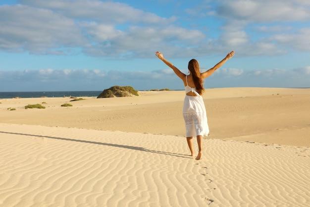 Tramonto nel deserto. giovane donna con con le braccia alzate che indossa un abito bianco che cammina nella sabbia delle dune del deserto durante il tramonto. ragazza sulla sabbia dorata su corralejo dunas, fuerteventura. Foto Premium