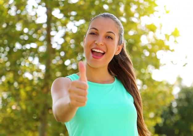 Superdonna! ritratto della ragazza del vincitore che mostra il pollice in su. donna in buona salute sorridente positiva di forma fisica all'aperto. Foto Premium