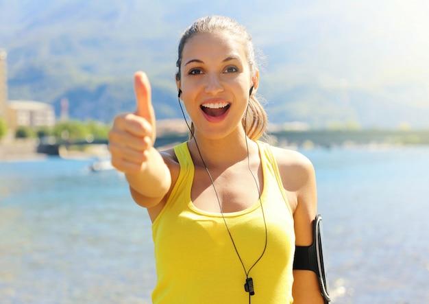 Superdonna! ritratto della ragazza del vincitore che mostra il pollice in su. donna sorridente positiva di forma fisica all'aperto. felice bella fitness donna abbigliamento attivo e fascia da braccio sportiva per allenamento telefono e auricolari sulla spiaggia. Foto Premium
