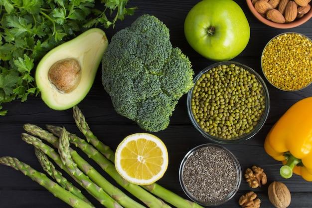 Superfood o concetto vegetariano dell'alimento verdure, frutta, legumi, polline matto e dell'ape sui precedenti di legno neri vista superiore. Foto Premium