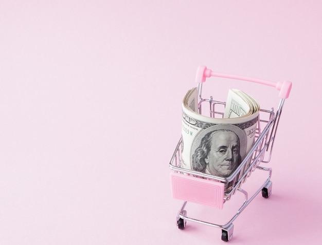 Carrello del supermercato pieno di banconote in dollari usa. libero scambio. mercato monetario. stile minimalista. carrello del negozio al supermercato. vendita, sconto Foto Premium
