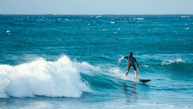 Surfer riding wave in vista di luce diurna lunga Foto Premium
