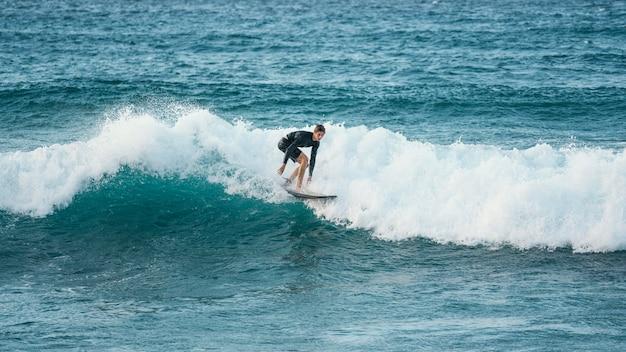 Surfer riding wave alla luce del giorno Foto Premium