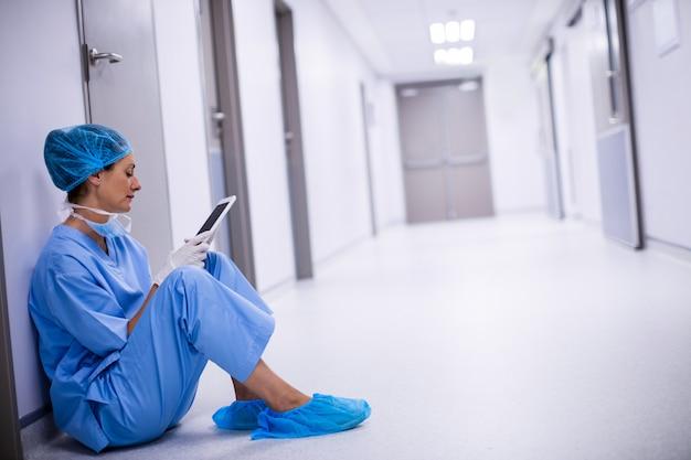 Chirurgo seduto sul pavimento e utilizzando la tavoletta digitale Foto Premium