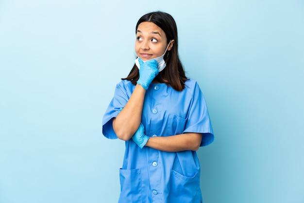 Donna del chirurgo sopra la parete blu isolata che pensa un'idea mentre osservando in su Foto Premium