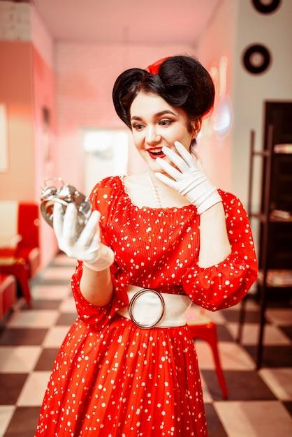 Ragazza pin up sorpresa guarda la sveglia, interni caffè vintage Foto Premium