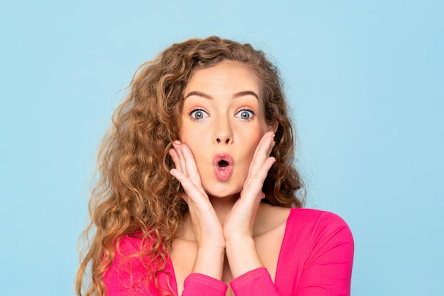Donna caucasica colpita sorpresa con gli occhi e le mani schioccati sulle guance in parete blu Foto Premium
