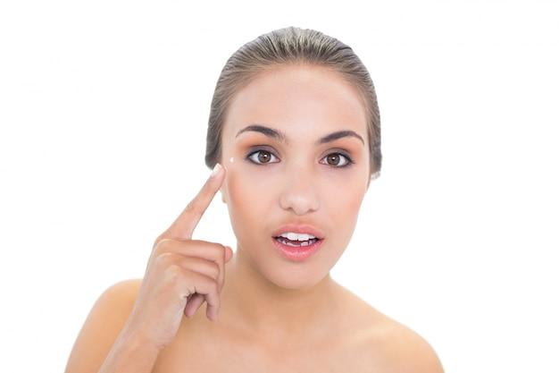 Sorpreso giovane donna bruna che punta al suo occhio Foto Premium