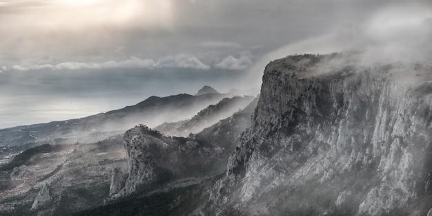 Paesaggio di montagna surreale con picchi nella nebbia Foto Premium