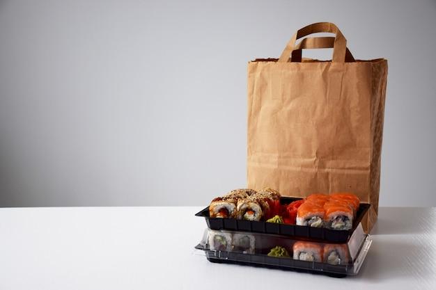 Rotoli di sushi in scatola di plastica vicino al pacchetto di carta sul tavolo bianco. consegna o da asporto concetto. Foto Premium