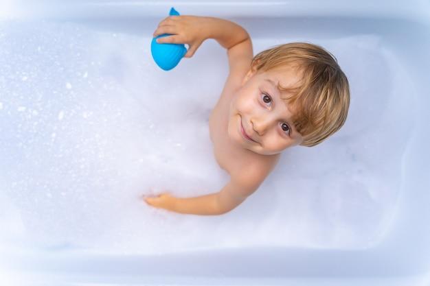 Ragazzo Biondo Dolce Del Bambino Che Gioca Con Il Giocattolo Facendo Il Bagno Nella Vasca Da Bagno Foto Premium