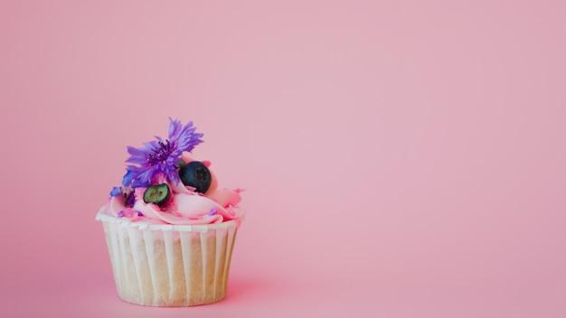 Dessert dolce sullo spazio rosa della copia. cupcake con panna, bello e delizioso. Foto Premium