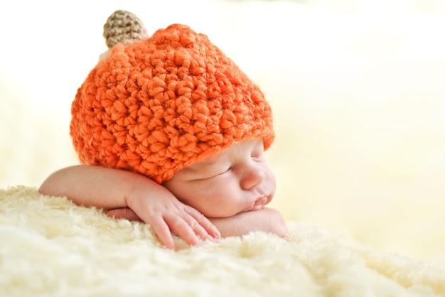 Bambino appena nato addormentato dolce che porta cappello della zucca Foto Premium