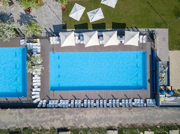 Piscina con acqua azzurra in estate e lettini bianchi con elemento esterno Foto Premium
