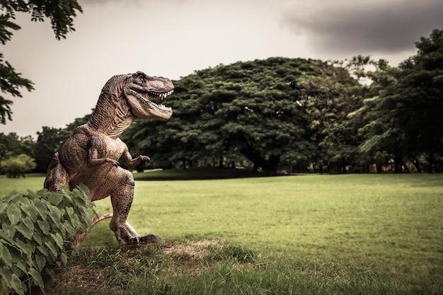T-rex con i rami degli alberi contro la natura Foto Premium