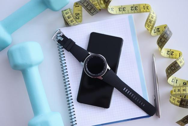 Sul tavolo ci sono il manubrio e il centimetro dell'orologio intelligente dello smartphone del pianificatore quotidiano Foto Premium