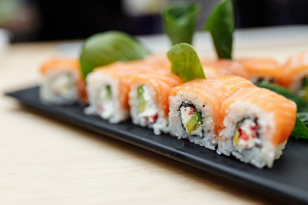 Sul tavolo sushi roll cibo pesce philadelphia giapponese salmone delizioso sushi riso cetriolo pasto tradizionale wasabi fresco sano gourmet crudo cucina. Foto Premium