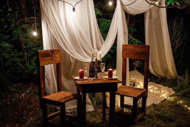 Tavolo nel bosco, cena romantica per due a lume di candela. tende bianche sull'albero, una ghirlanda di Foto Premium