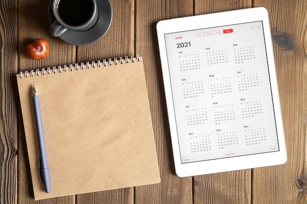 Un tablet con un calendario aperto per l'anno 2021, una tazza di caffè, castagne e un taccuino di carta artigianale su un tavolo di assi di legno Foto Premium