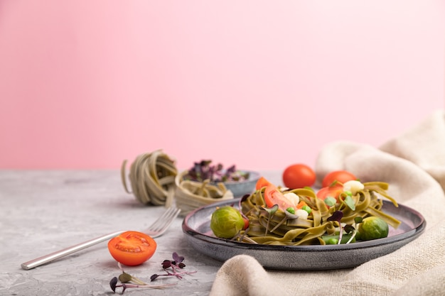 Tagliatelle verdi di spinaci con pomodoro, piselli e germogli microgreen. vista laterale, copia dello spazio. Foto Premium