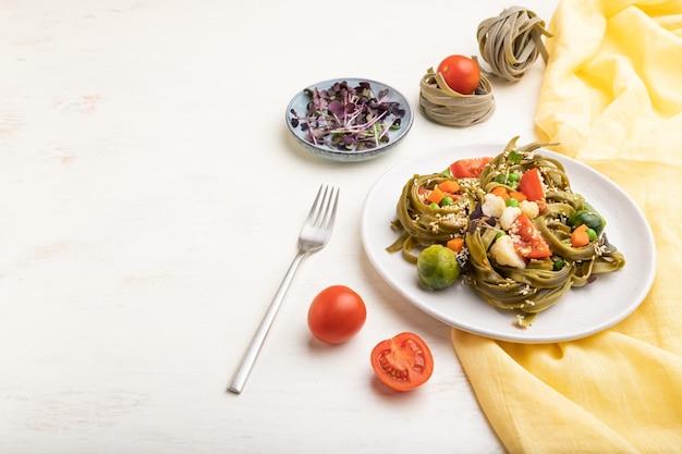 Tagliatelle di spinaci verdi pasta con pomodoro, piselli e germogli microgreen su un tavolo in legno bianco e giallo tessile. vista laterale, copia dello spazio. Foto Premium