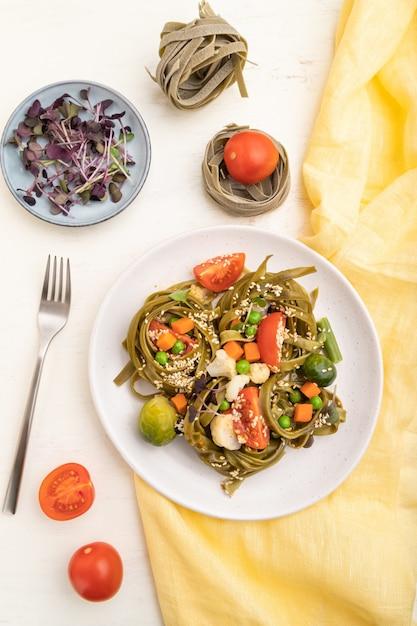 Tagliatelle di spinaci verdi pasta con pomodoro, piselli e germogli microgreen su un tavolo in legno bianco e giallo tessile. vista dall'alto, piatto laico, da vicino. Foto Premium