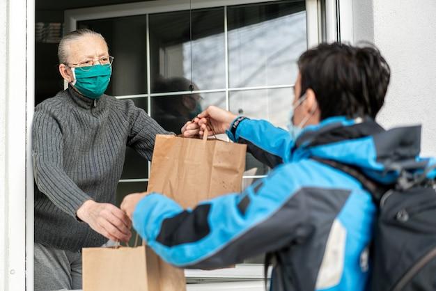 Prendersi cura delle persone anziane durante la pandemia fornendo loro Foto Premium