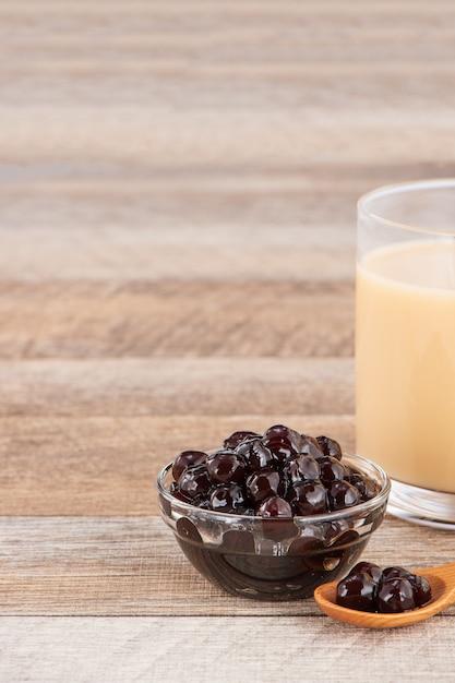 Tapioca pearl, bubble topping per tè o altra bevanda, in una tazza, posto su un tavolo di legno. copia spazio Foto Premium