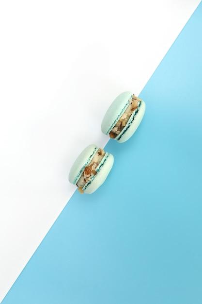 Gustosi macarons francesi blu o amaretti su uno sfondo bianco e blu. geometria del colore. Foto Premium