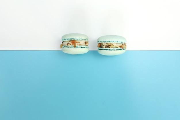 Gustosi macarons francesi blu o amaretti su uno sfondo bianco e blu. posto per il testo. Foto Premium
