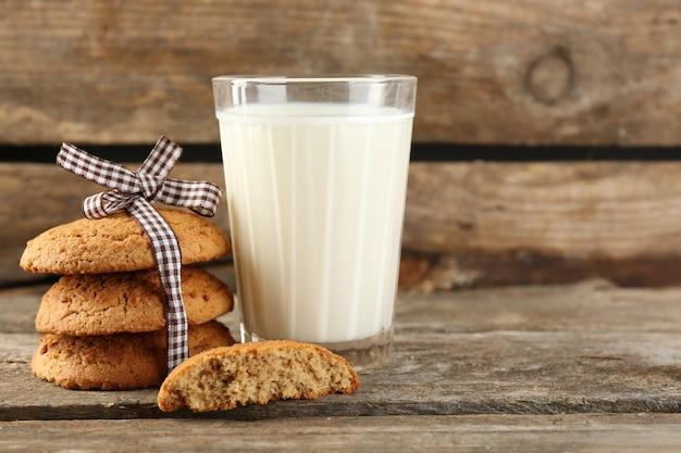 Gustosi biscotti e bicchiere di latte su legno rustico Foto Premium