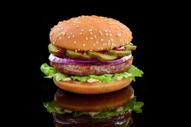 Gustosi hamburger fatti in casa alla griglia con carne di manzo. su uno sfondo nero Foto Premium