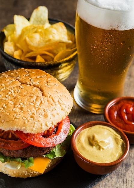 Gustoso hamburger con un bicchiere di birra e patatine Foto Premium