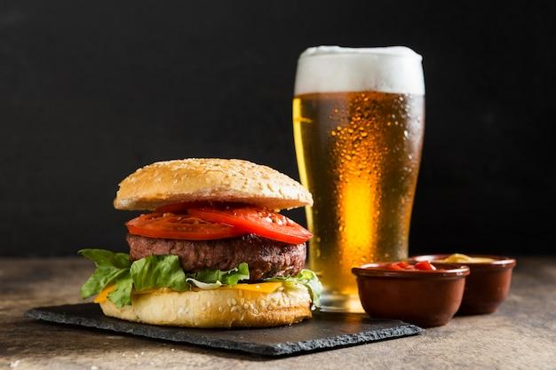 Gustoso hamburger con un bicchiere di birra e salsa ketchup Foto Premium