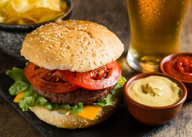 Gustoso hamburger con un bicchiere di birra e senape Foto Premium