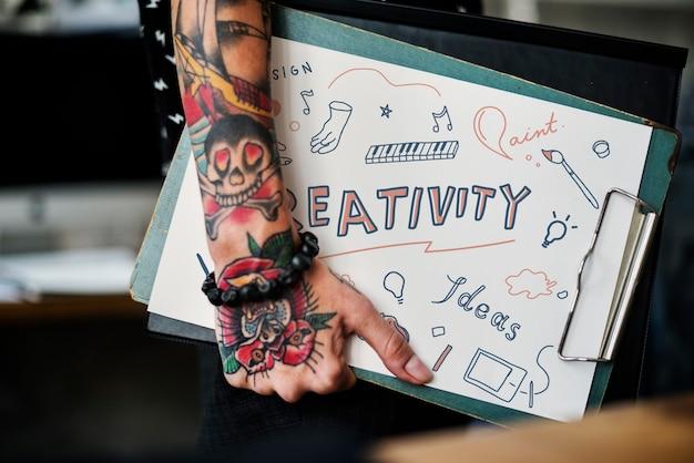 Mano tatuata che tiene una lavagna per appunti di creatività Foto Premium