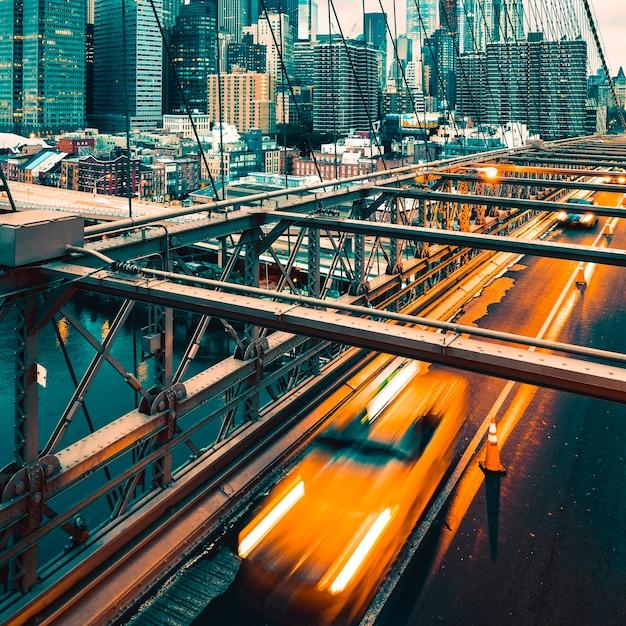 Taxi che attraversa il ponte di brooklyn a new york, skyline di manhattan in background Foto Premium