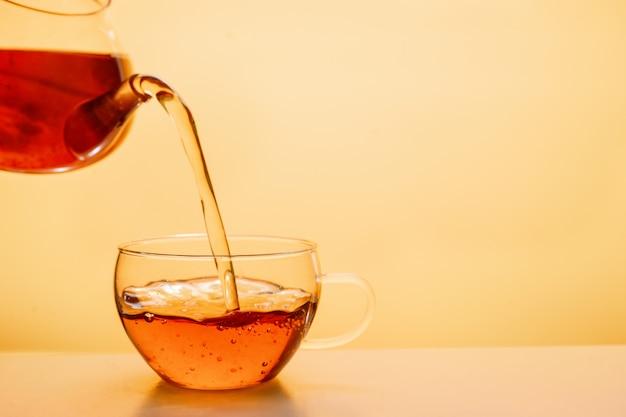 Il tè viene versato nella tazza di tè di vetro Foto Premium