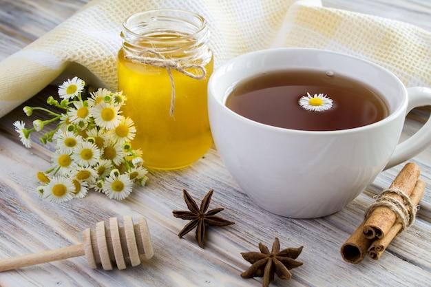 Tè, miele, cannella e camomille su legno Foto Premium