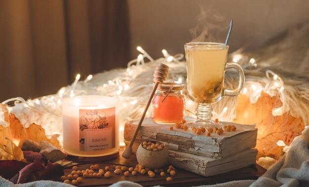 Tè con bacche di olivello spinoso e zenzero su libri antichi, miele, candela e foglie d'autunno. l'atmosfera di comfort a casa. calda casa accogliente. Foto Premium