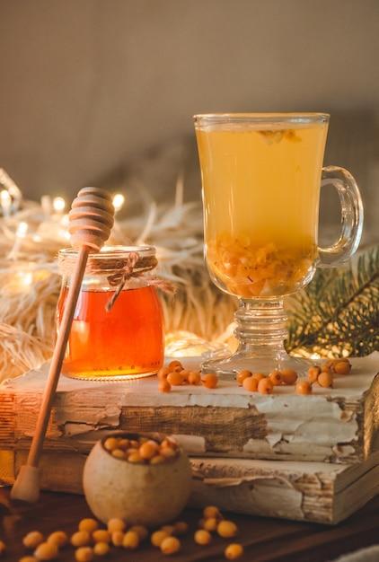 Tè con bacche di olivello spinoso e zenzero su libri antichi, miele, candele e rami di conifere. l'atmosfera di comfort a casa. calda casa accogliente. Foto Premium